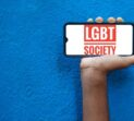 LGBT society Word on smart phone screen isolated on blue background with copy space for text. Person holding mobile on his hand and showing front of LGBT Society.(Lesbi, Gay, Bisexual, Transgender).